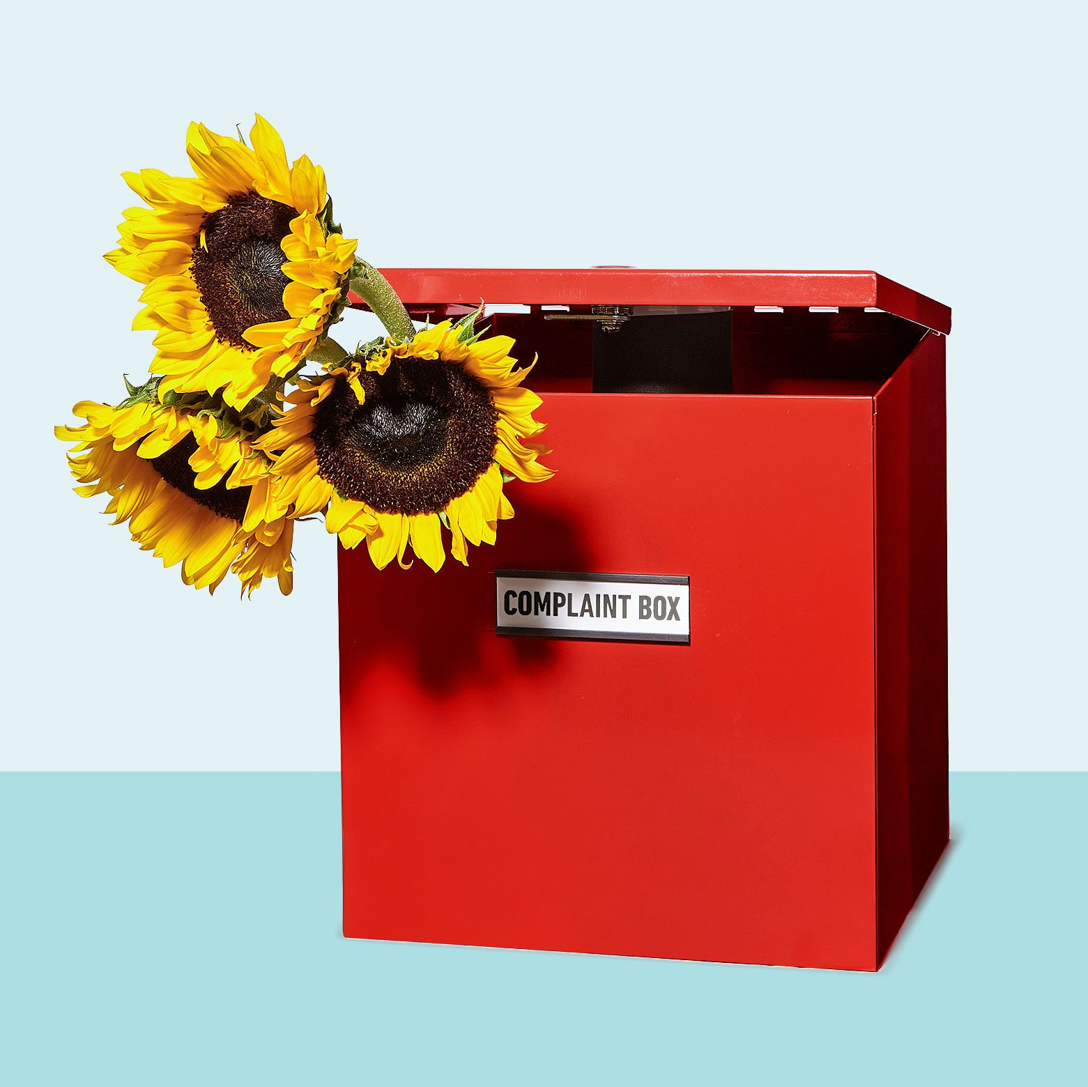 red complaint box with a bundle of sunflowers sticking out