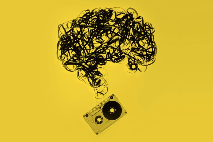 vintage cassette tape with the tape pulled out and formed into the shape of a brain