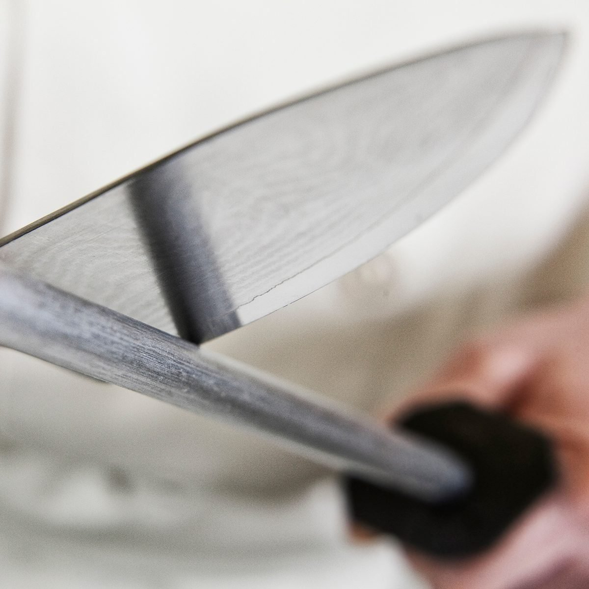 Close-up of a chef sharpening a large kitchen knife blade with a steel.