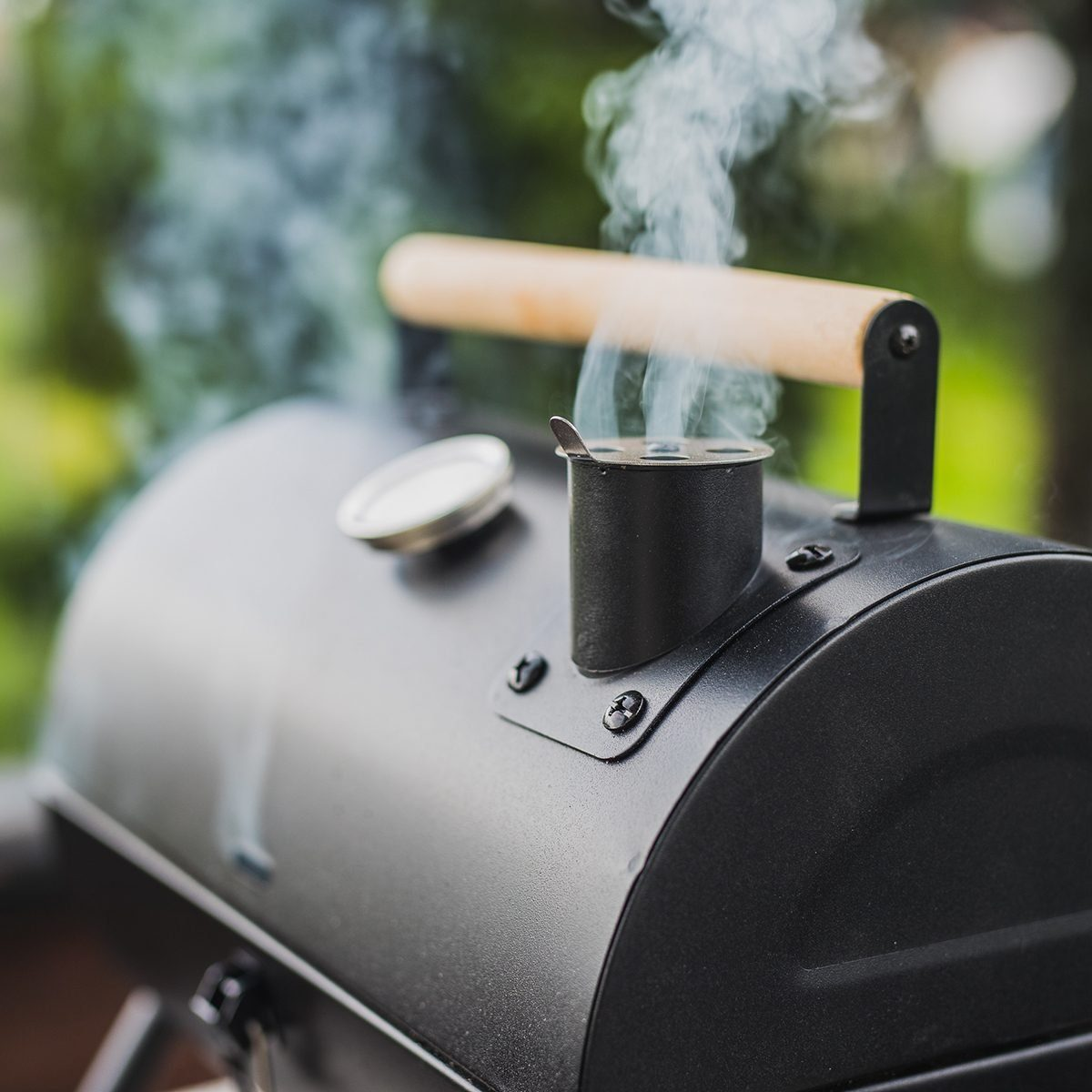 Smoke coming out of a smokestack of a small black smoker grill or barbecue on green background.; Shutterstock ID 1408814591; Job (TFH, TOH, RD, BNB, CWM, CM): TOH