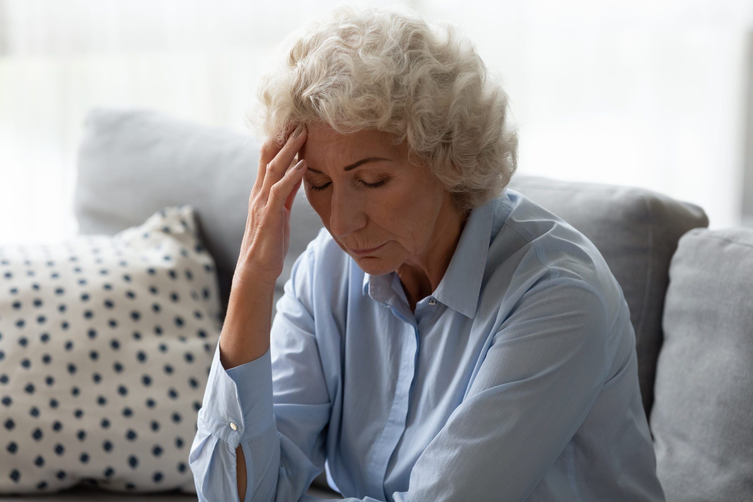 Sick senior woman sit on sofa at home feel distressed suffer from migraine or headache, ill mature female rest on couch touch head have dizziness from high blood pressure, elderly healthcare concept