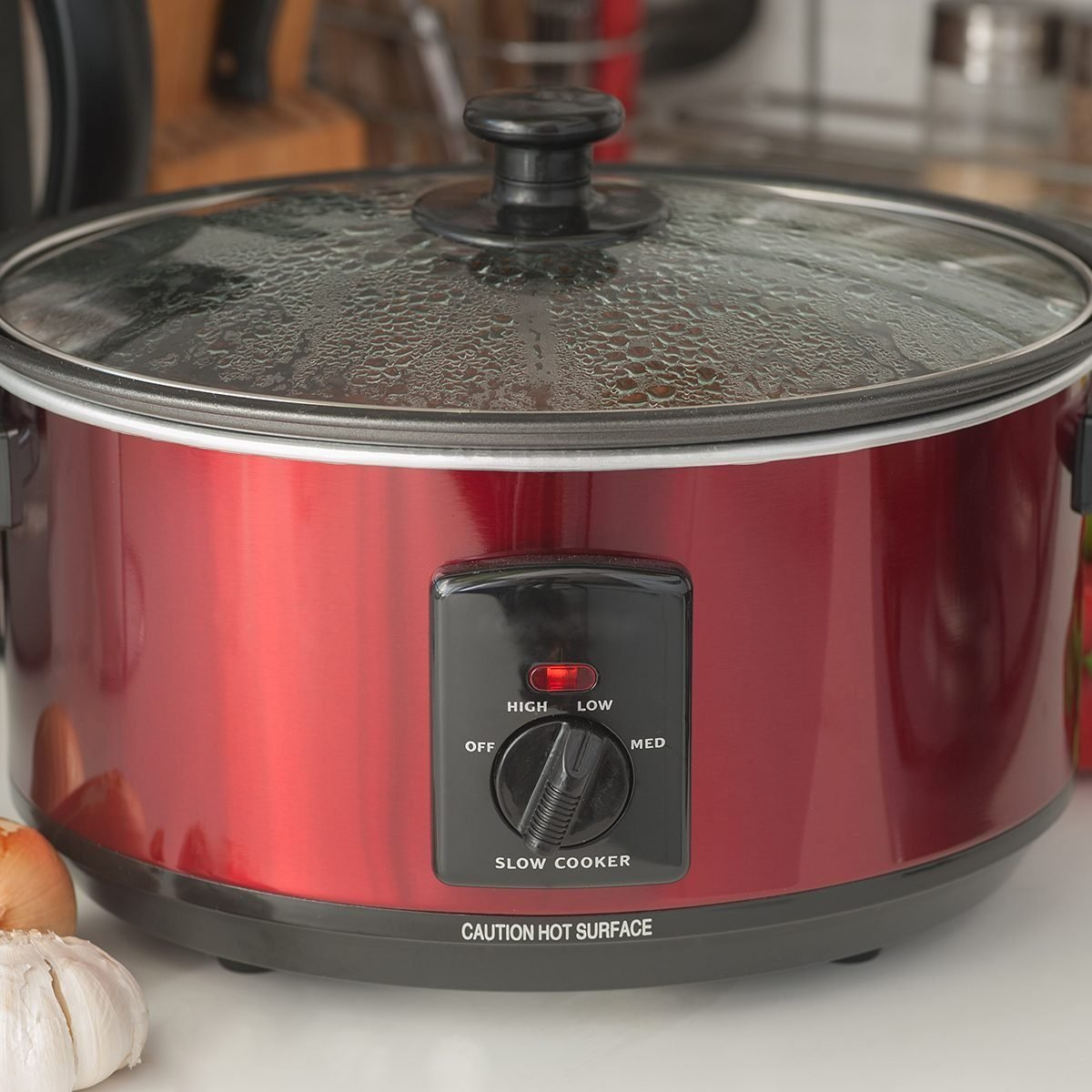Close up of a slow cooker working on kitchen shelf; Shutterstock ID 310888622