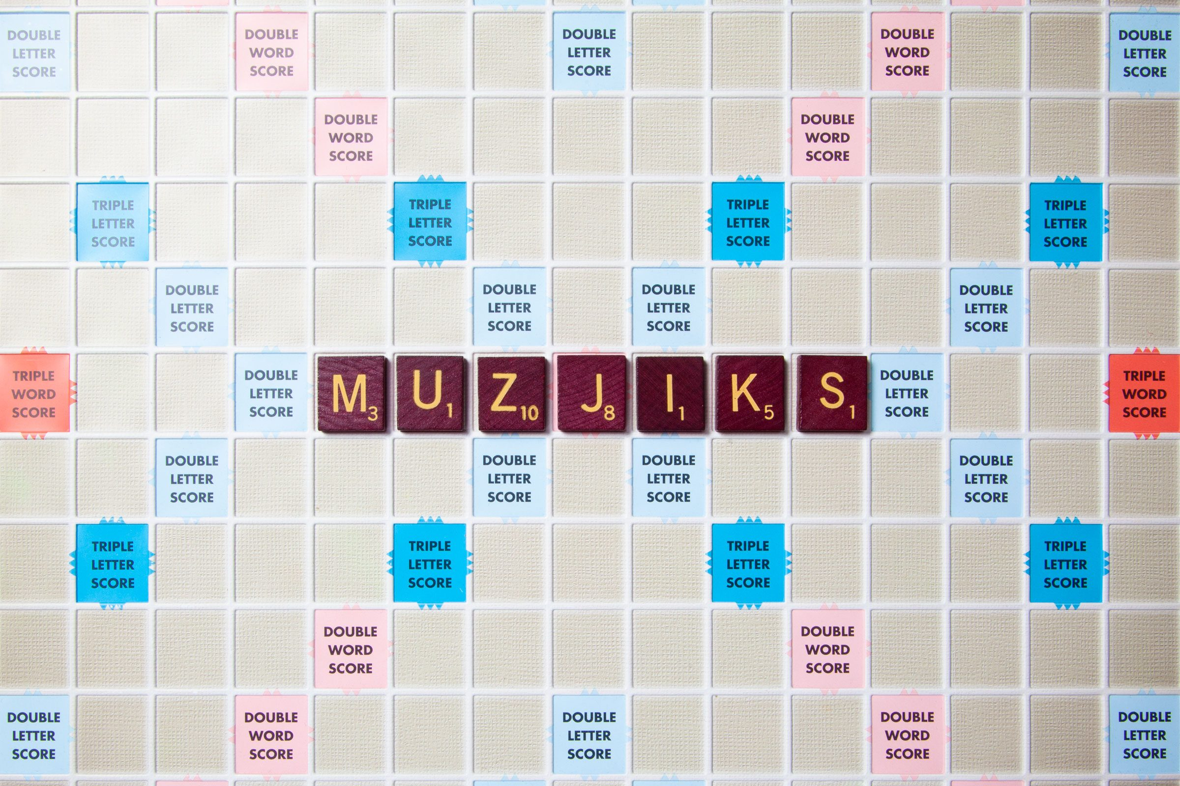 scrabble board with tiles that spell out muzjiks