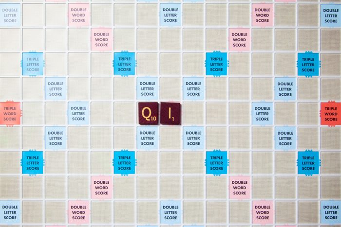 scrabble board with tiles that spell out qi