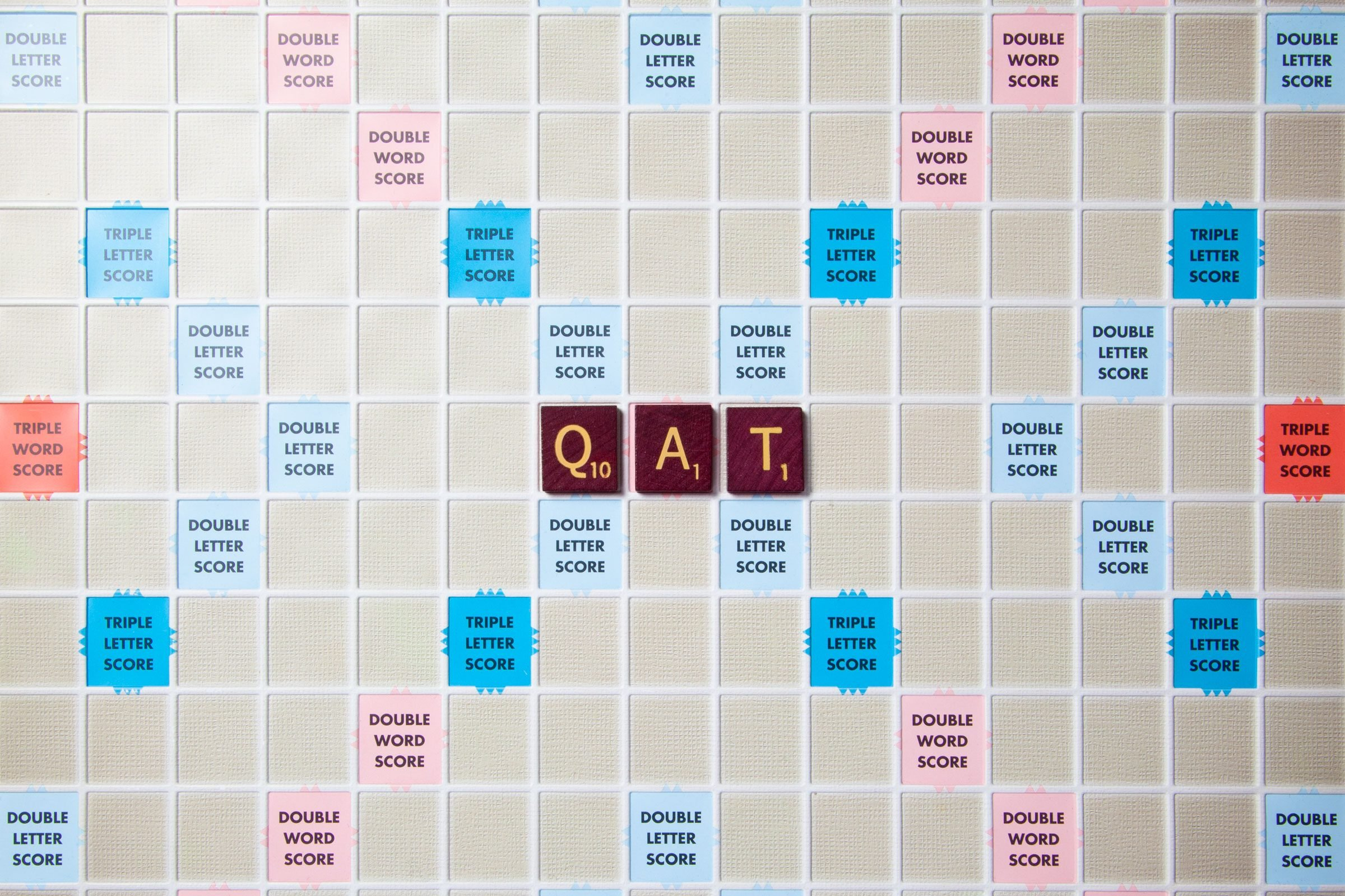 scrabble board with tiles that spell out qat