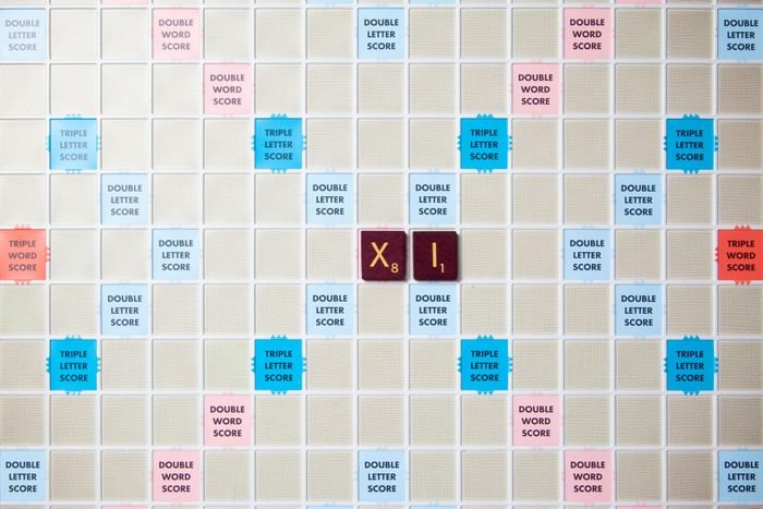 scrabble board with tiles that spell out xi