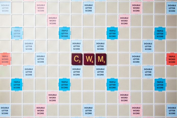 scrabble board with tiles that spell out cwm