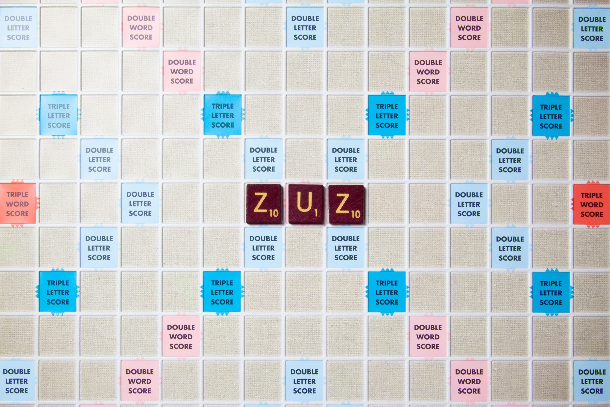 scrabble board with tiles that spell out zuz