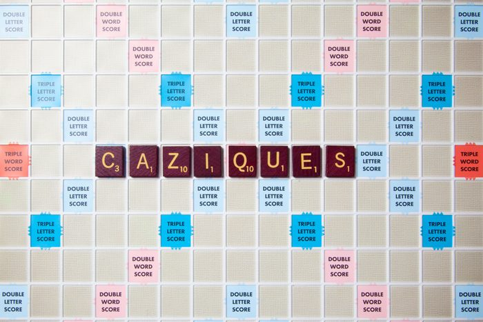 scrabble board with tiles that spell out caziques
