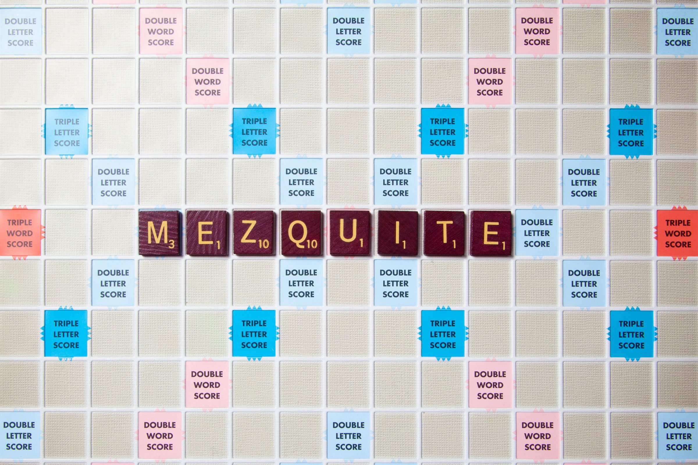 scrabble board with tiles that spell out mezquite