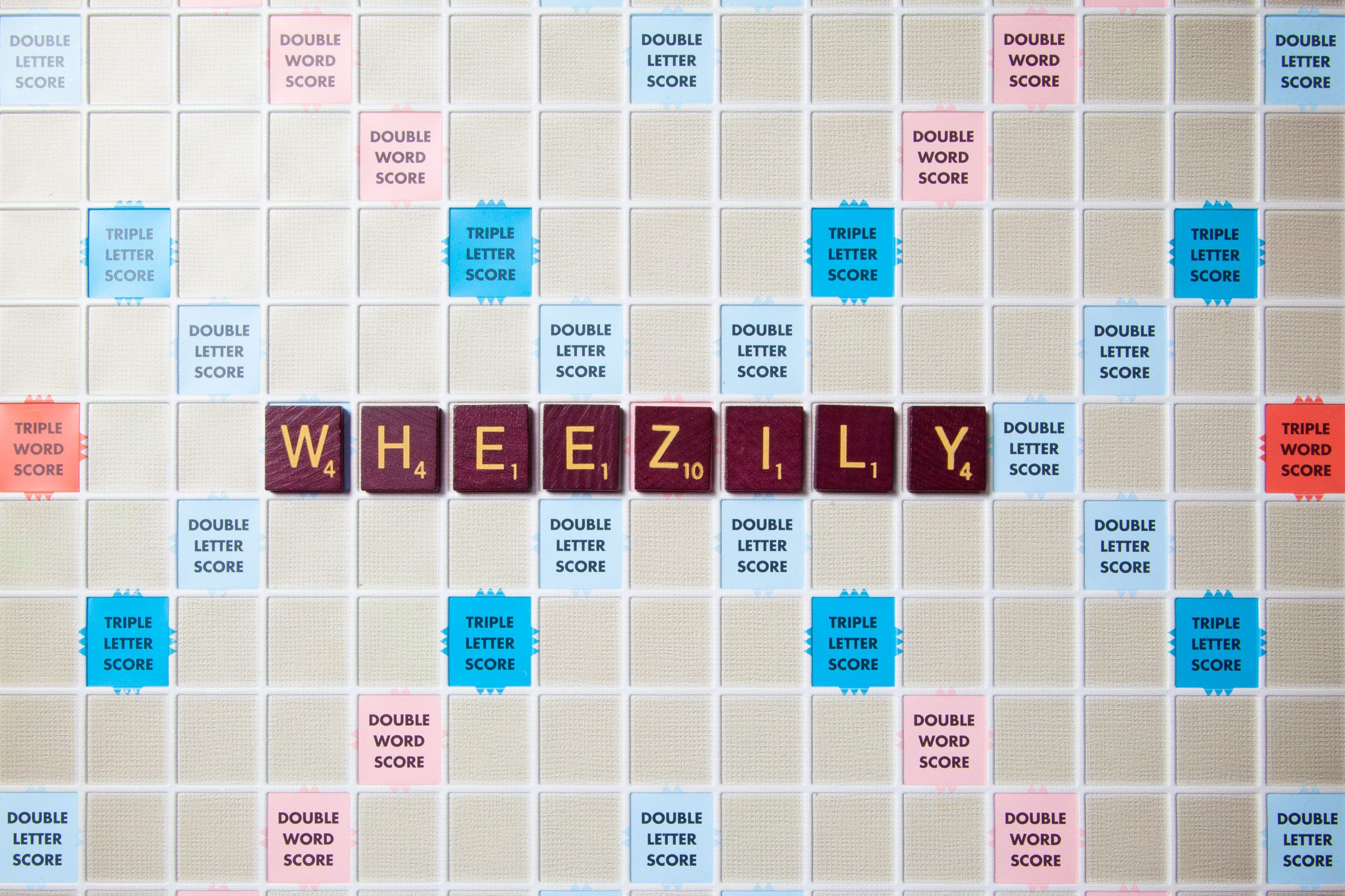 scrabble board with tiles that spell out wheezily