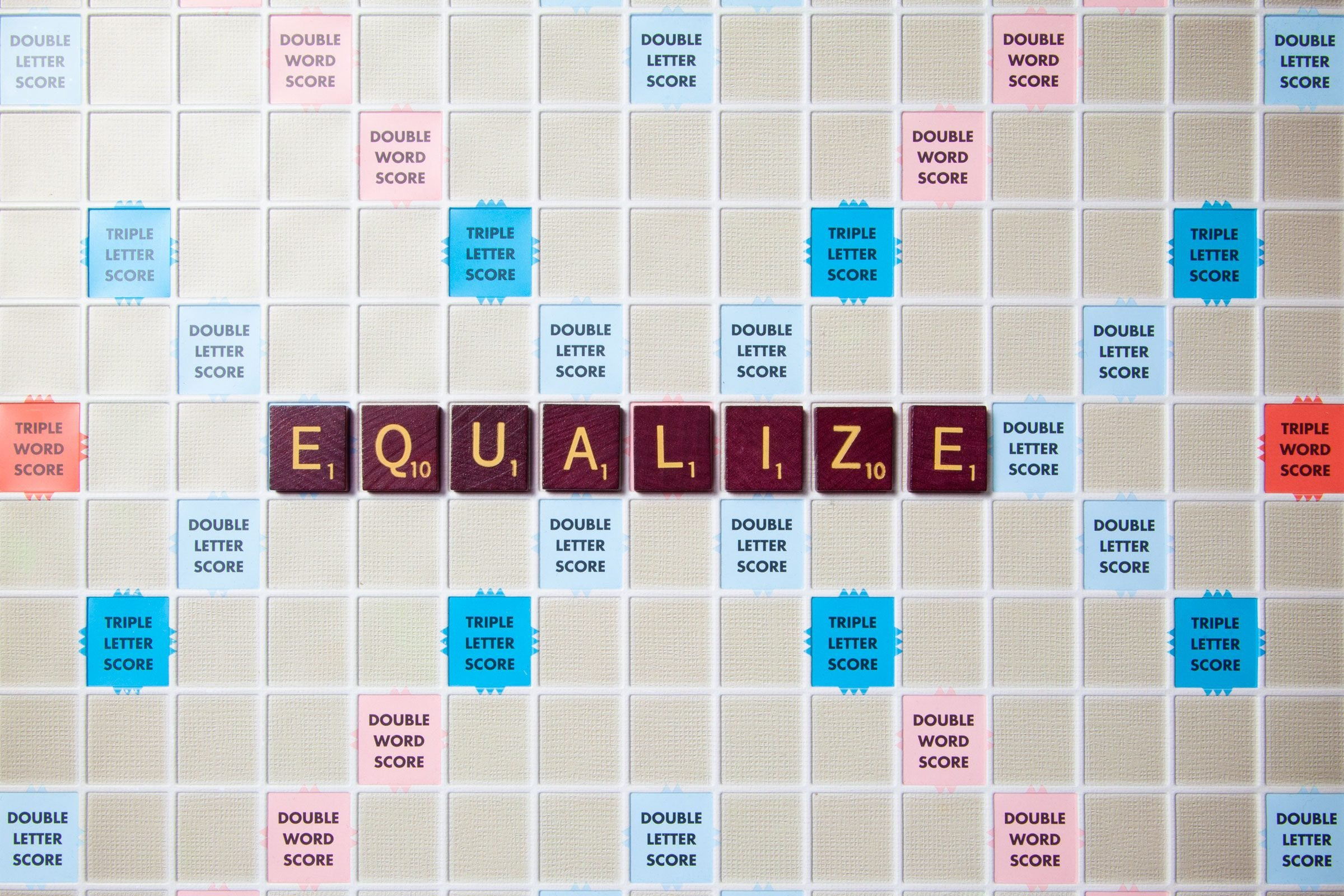 scrabble board with tiles that spell out equalize