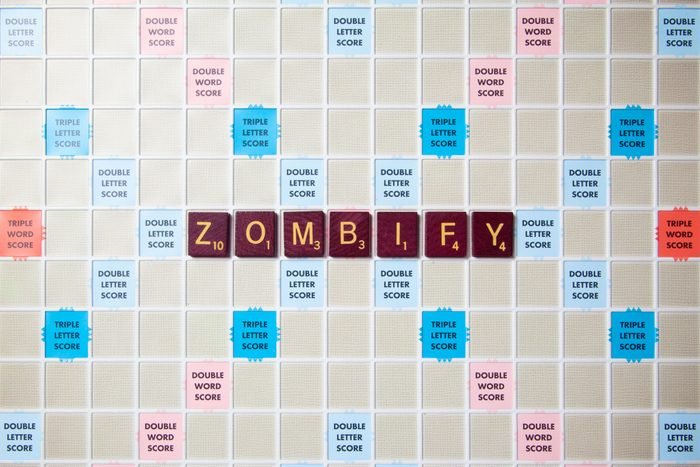 scrabble board with tiles that spell out zombify