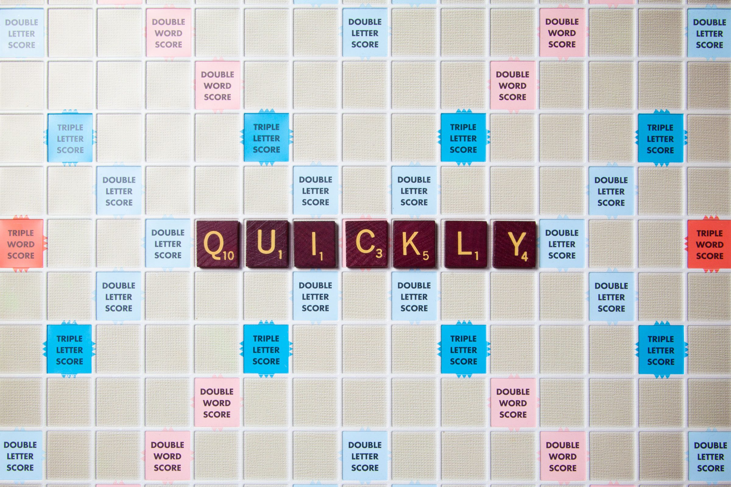 scrabble board with tiles that spell out quickly