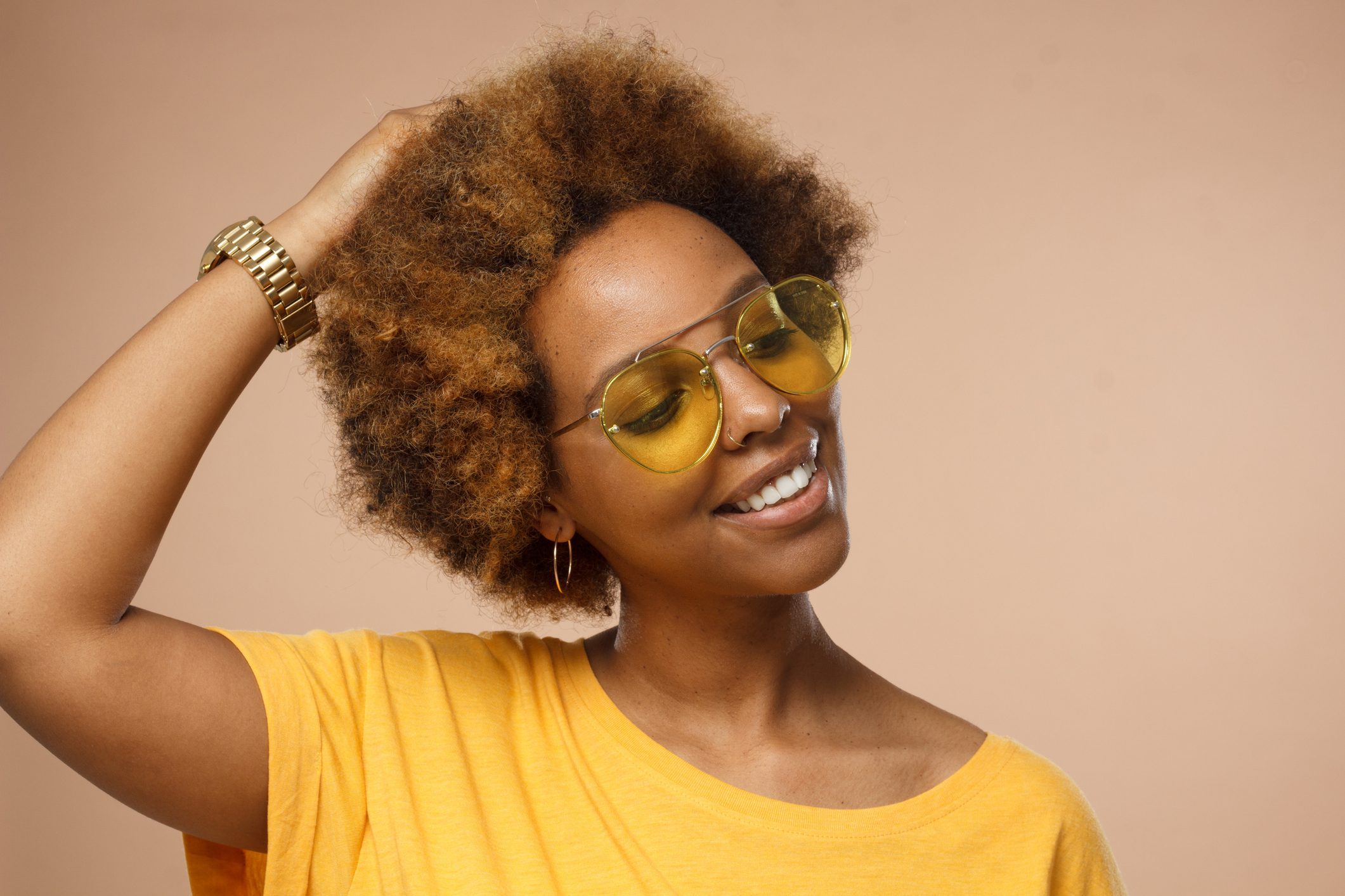 Studio closeup of attractive dark-skinned woman pictured against beige background wearing sunglasses and wristwatch looking down with charming smile as if dreaming or thinking about nice moments