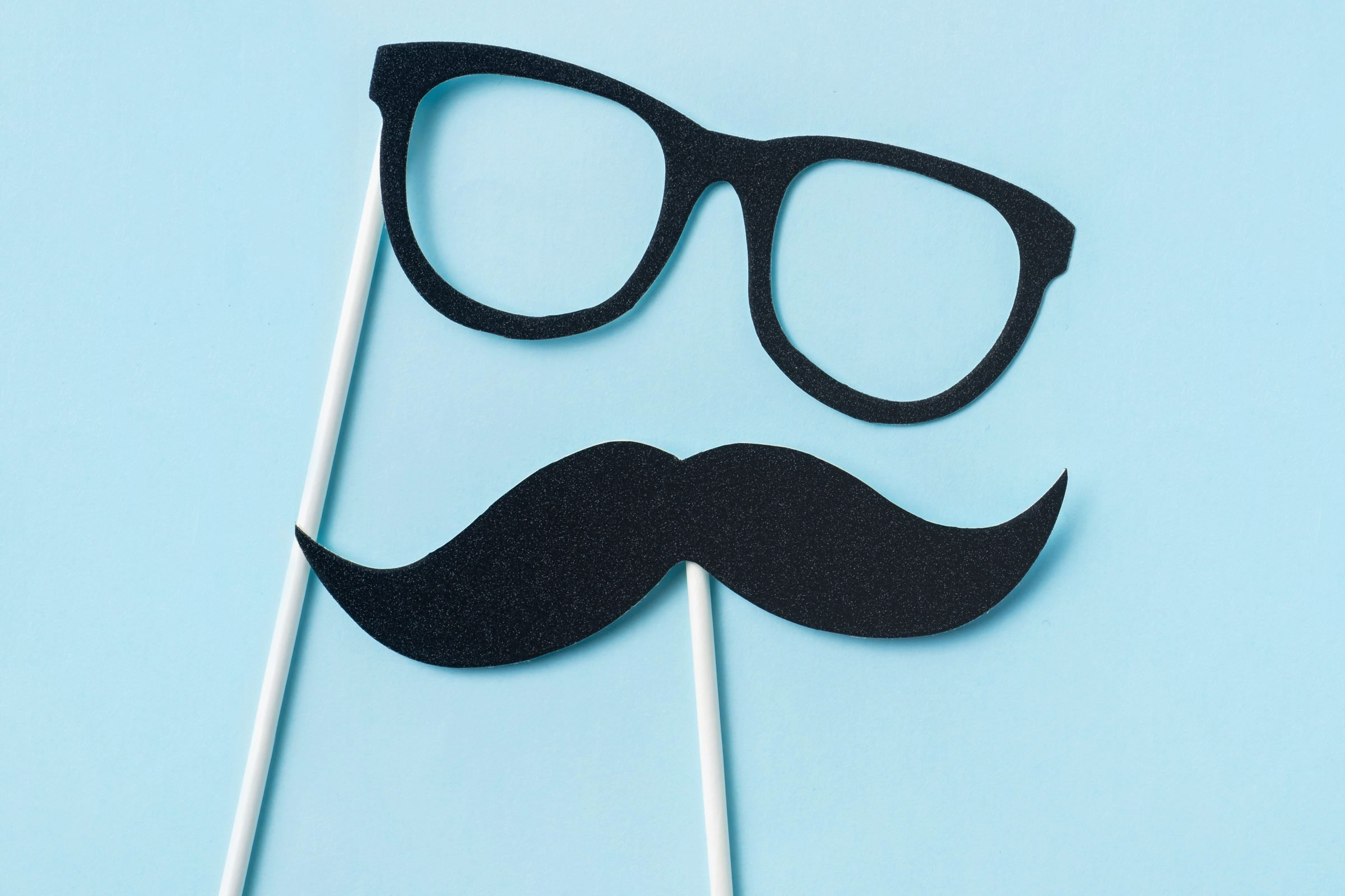 glasses and mustache photo booth props on blue background
