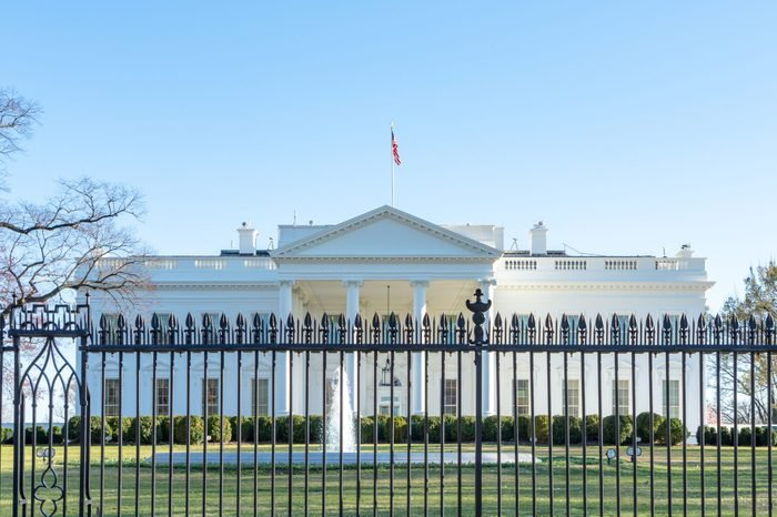 View of the white house in washington d.c. from afar, obstructed by the fence