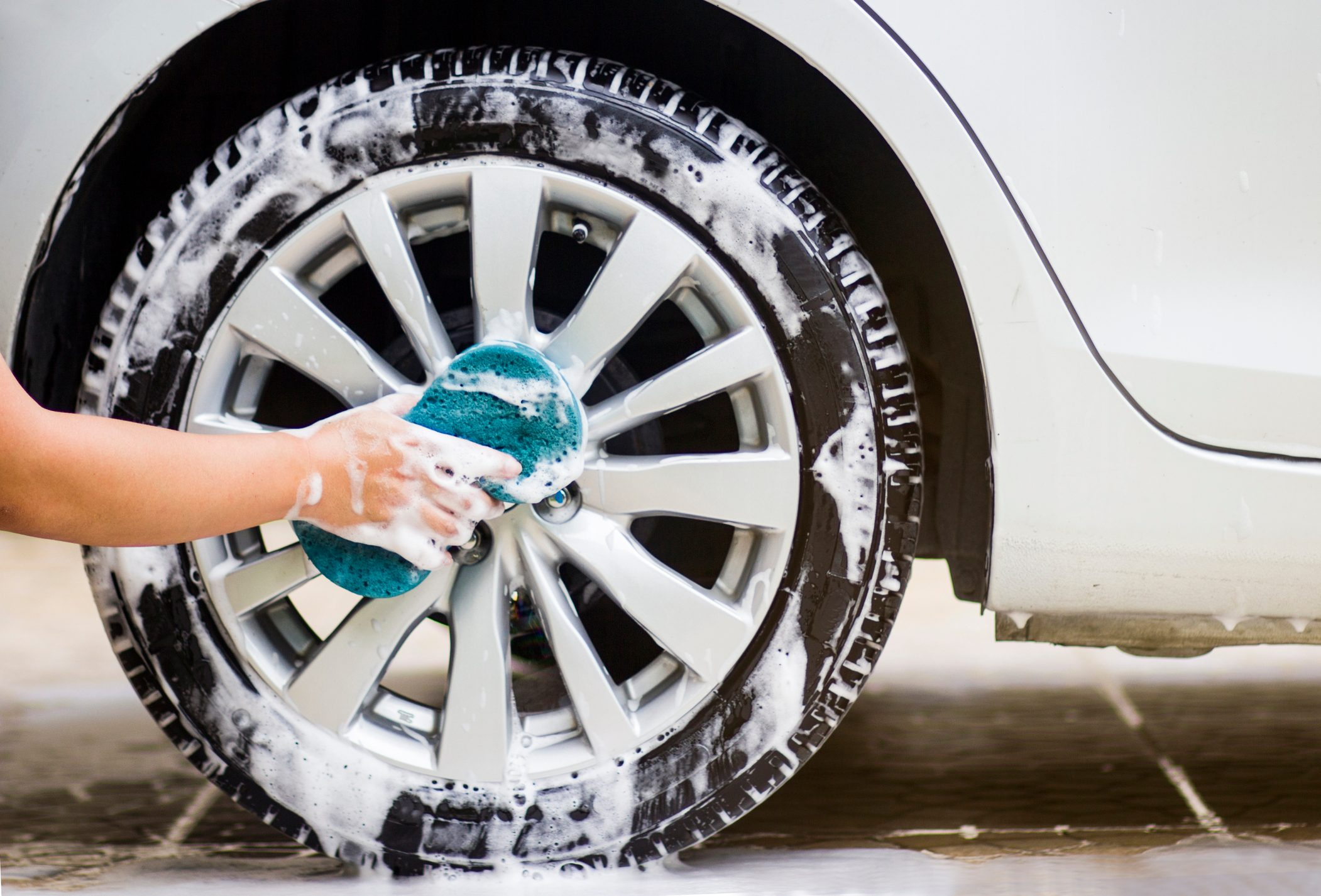 Cropped Hand Washing Tire Of Car