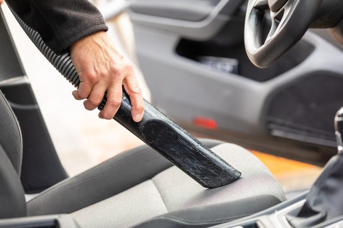 Cropped Hand Of Man Using Vacuum Cleaner In Car