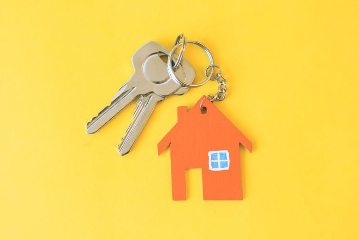silver keys with a house shaped keychain on yellow background