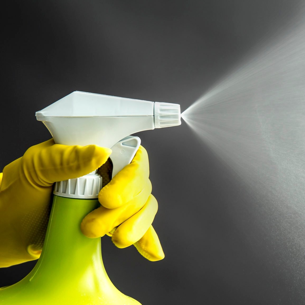 Woman wearing yellow rubber gloves using green spray bottle and spraying liquid mist in air, cool lighting effect. Lot of copy space.