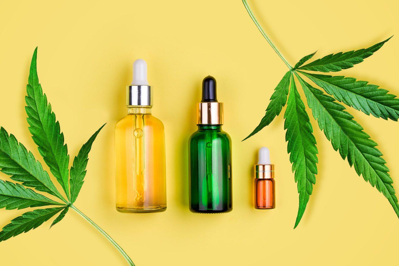 Glass bottles with CBD oil, THC tincture and hemp leaves on yellow background. Flat lay, minimalism. Cosmetics CBD hemp oil. Banner