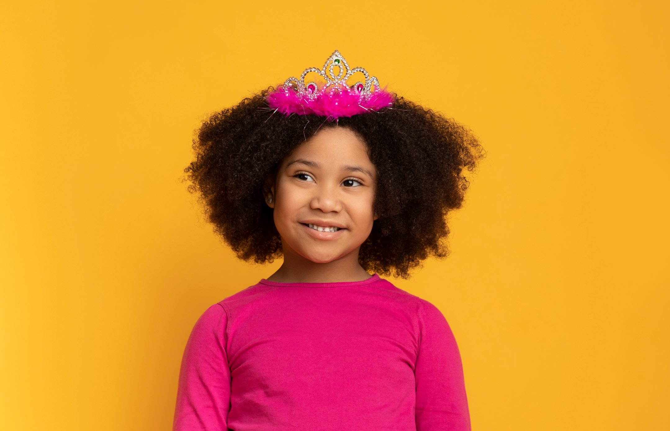 Portrait of charming little african american girl wearing princess crown
