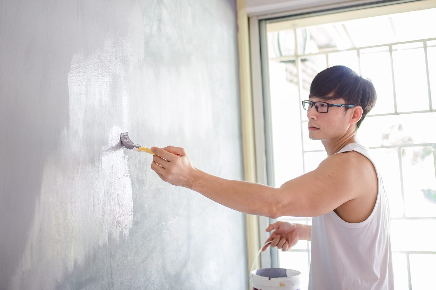 An Asia Chinese mature man painting walls using paint brush in his new house. Home makeover and renovation concept.