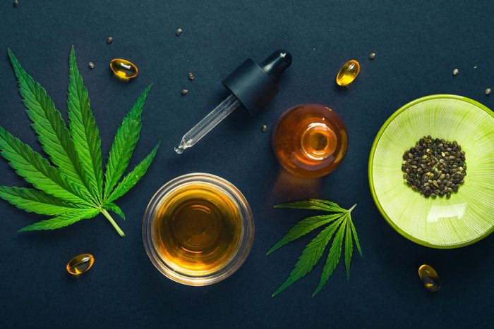 CBD oil, tincture with hemp leaves on a black background. Different bottles with a pipette and marijuana leaves.