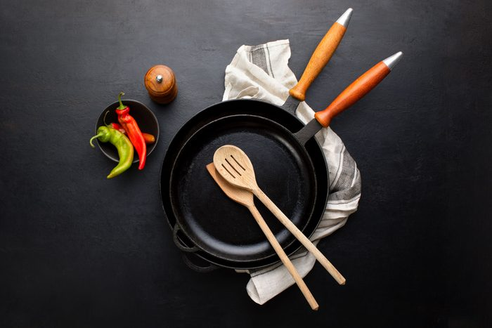 overhead view of two stacked cast iron skillet pans with crossed kitchen utensils