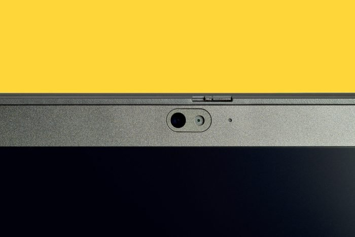 Part of a Computer monitor front camera lens. Web Camera on laptop isolated on yellow background.