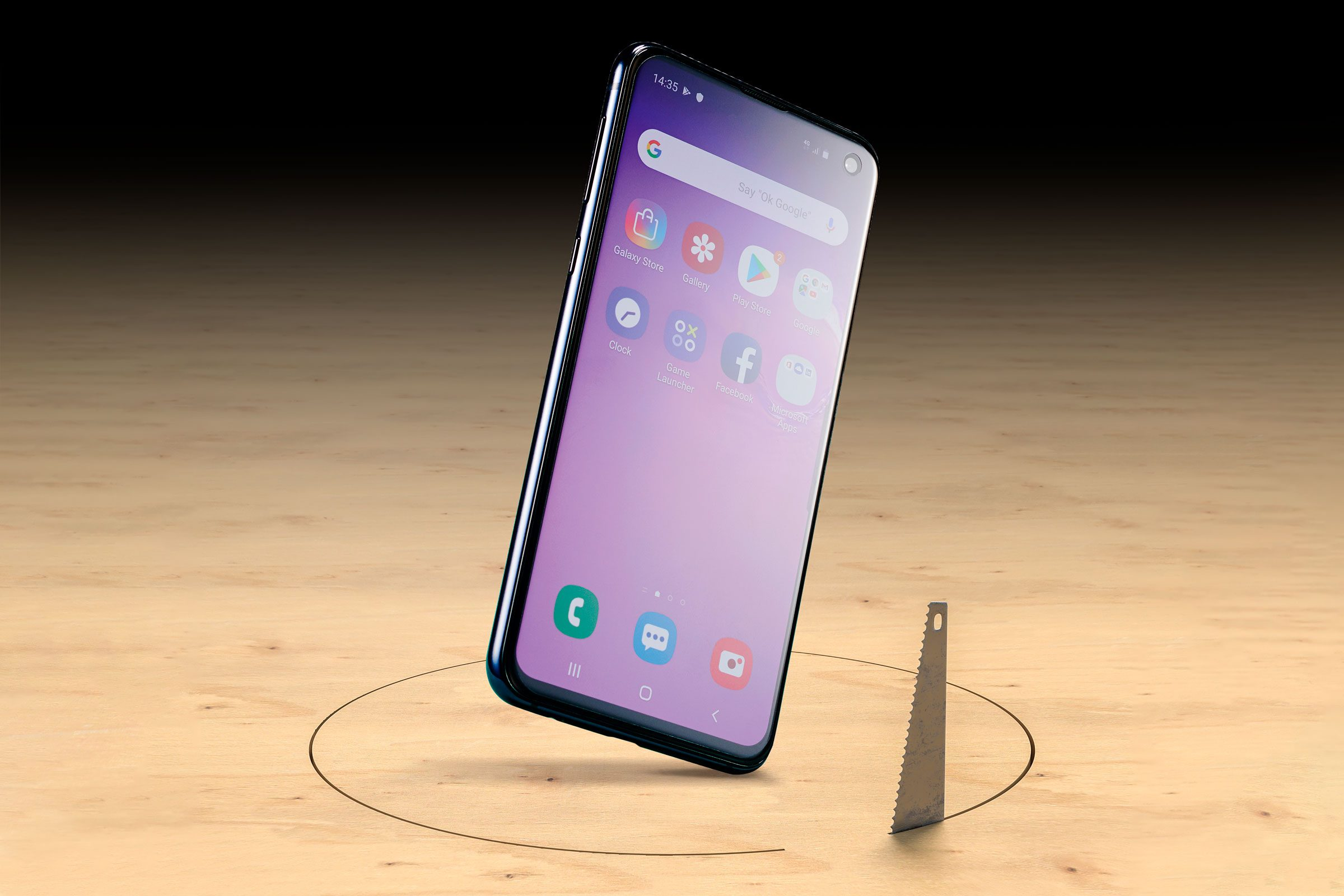 a smartphone stands on edge on wooden floor where a saw is cutting a circle around the floor from below