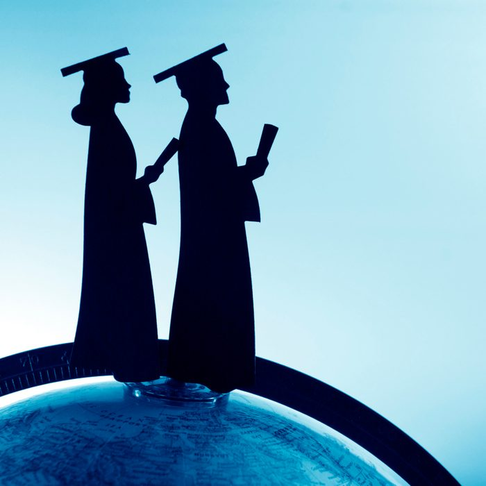 Male and female graduates holding diplomas stand on the top of the world.