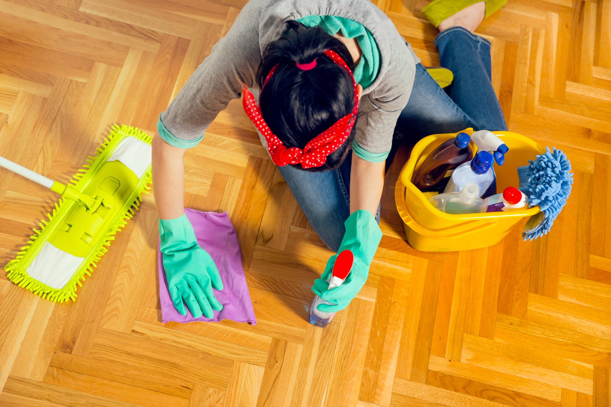 Young woman cleaning floor at home. View from above.
