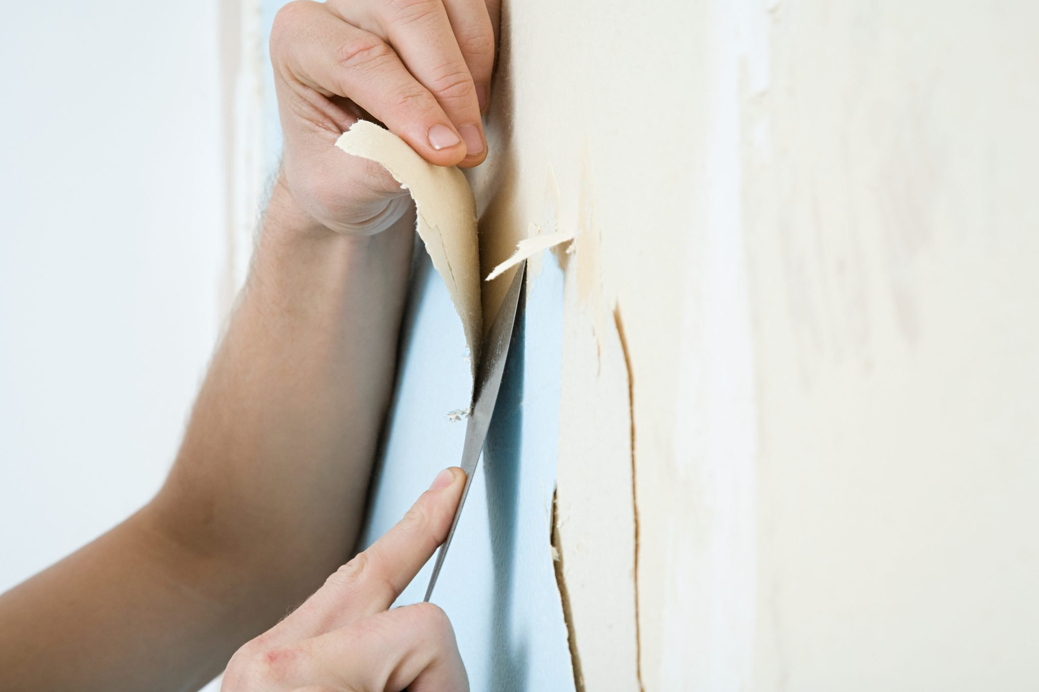 Person removing wallpaper