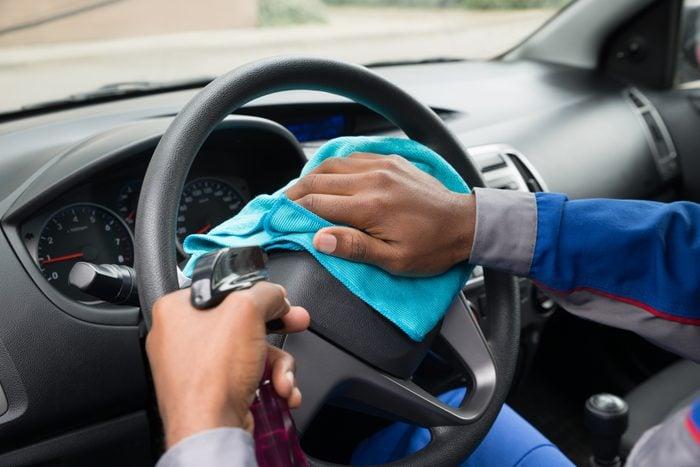 Worker Wiping Steering Wheel In Car