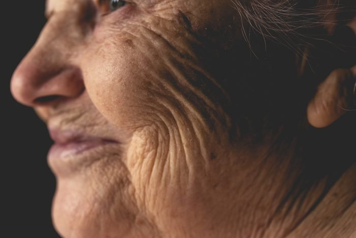 Wrinkled face of elderly woman, smiling details
