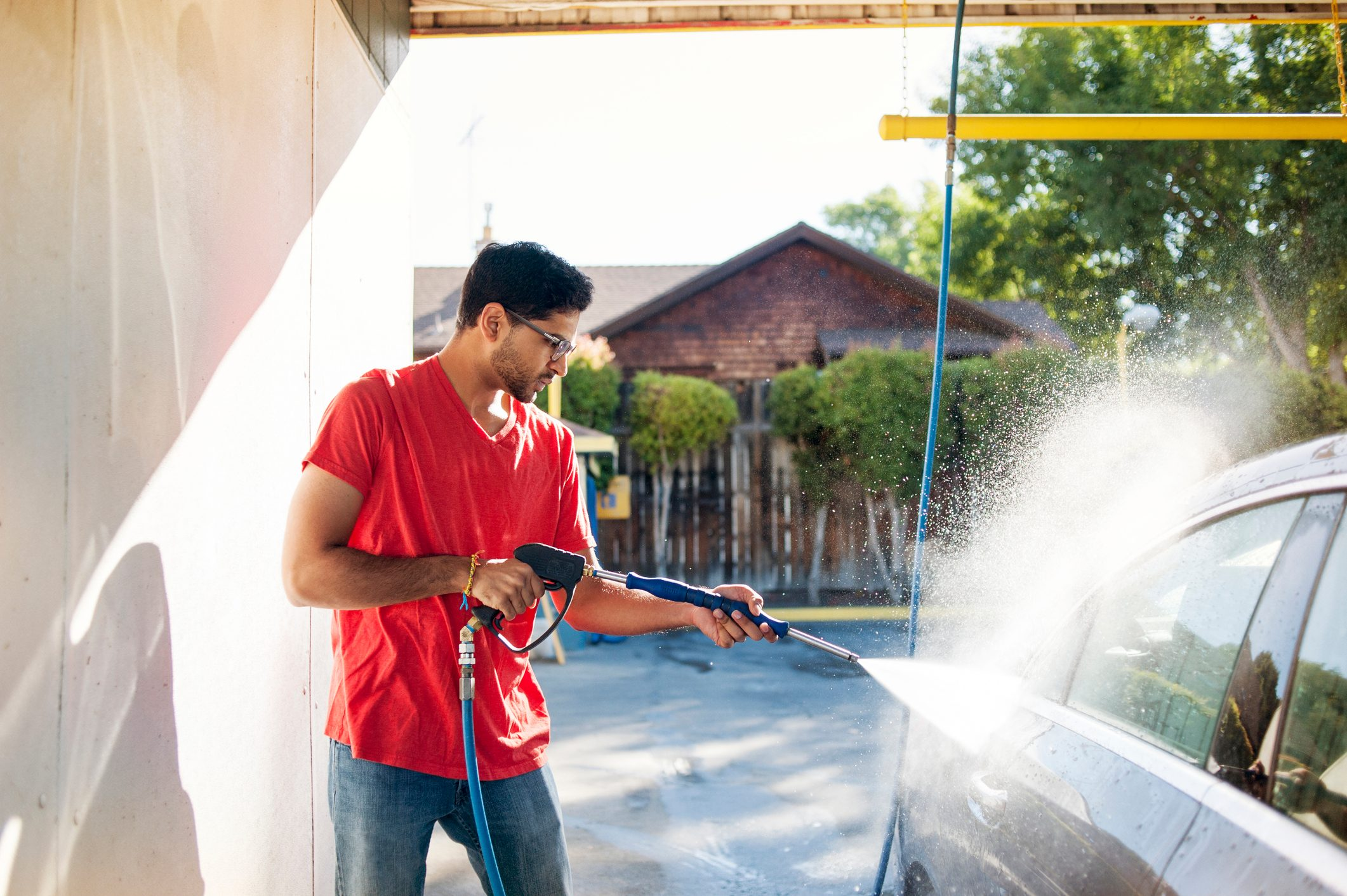 Man washing car in garage on sunny day