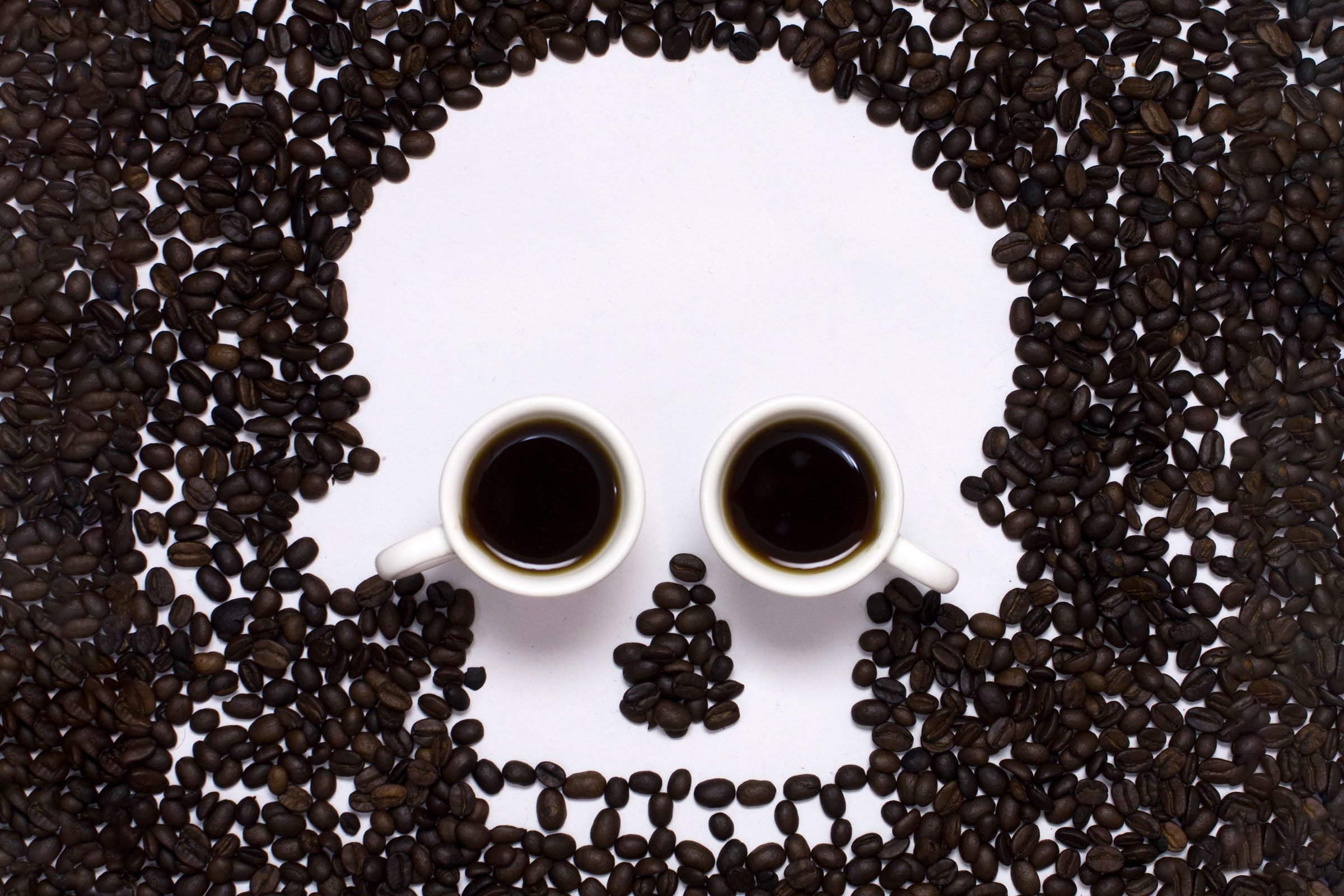 coffee beans shaped into a skull image with two coffee cups for eyes