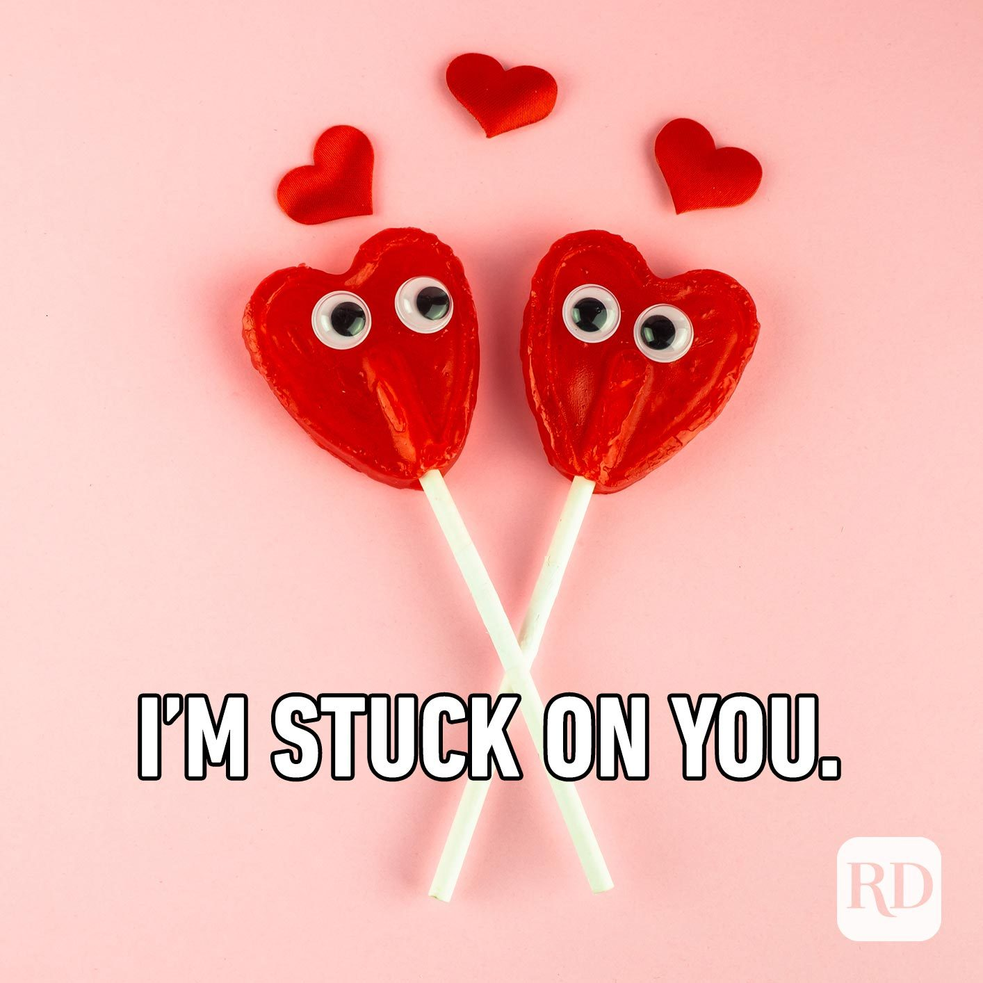 Two heart-shaped lollipops with googly eyes. Meme text: I'm stuck on you.