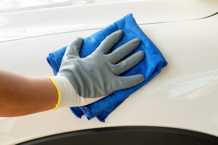 Car detailing - the man holds the microfiber in hand and polishes the car. Selective focus.