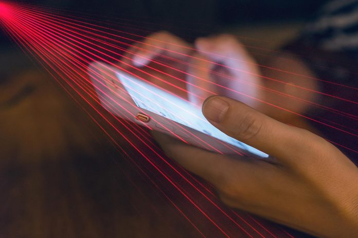 """Laserbeams scanning phone to represent a spy watching phone activity or """"spyware"""""""