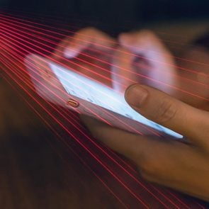 Laserbeams scanning phone to represent a spy watching phone activity or
