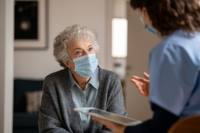 Senior woman wearing safety protective mask at home and talking to nurse. Back view of young doctor visiting old woman for routine health checkup during covid-19, coronavirus and flu outbreak.