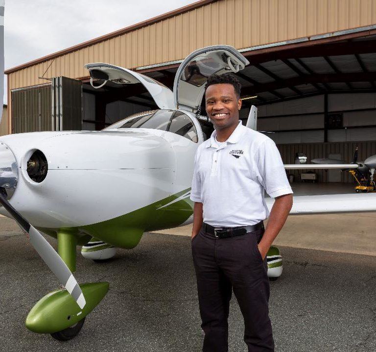 Courtland Savage, a black pilot, standing in front of a small propellor plane