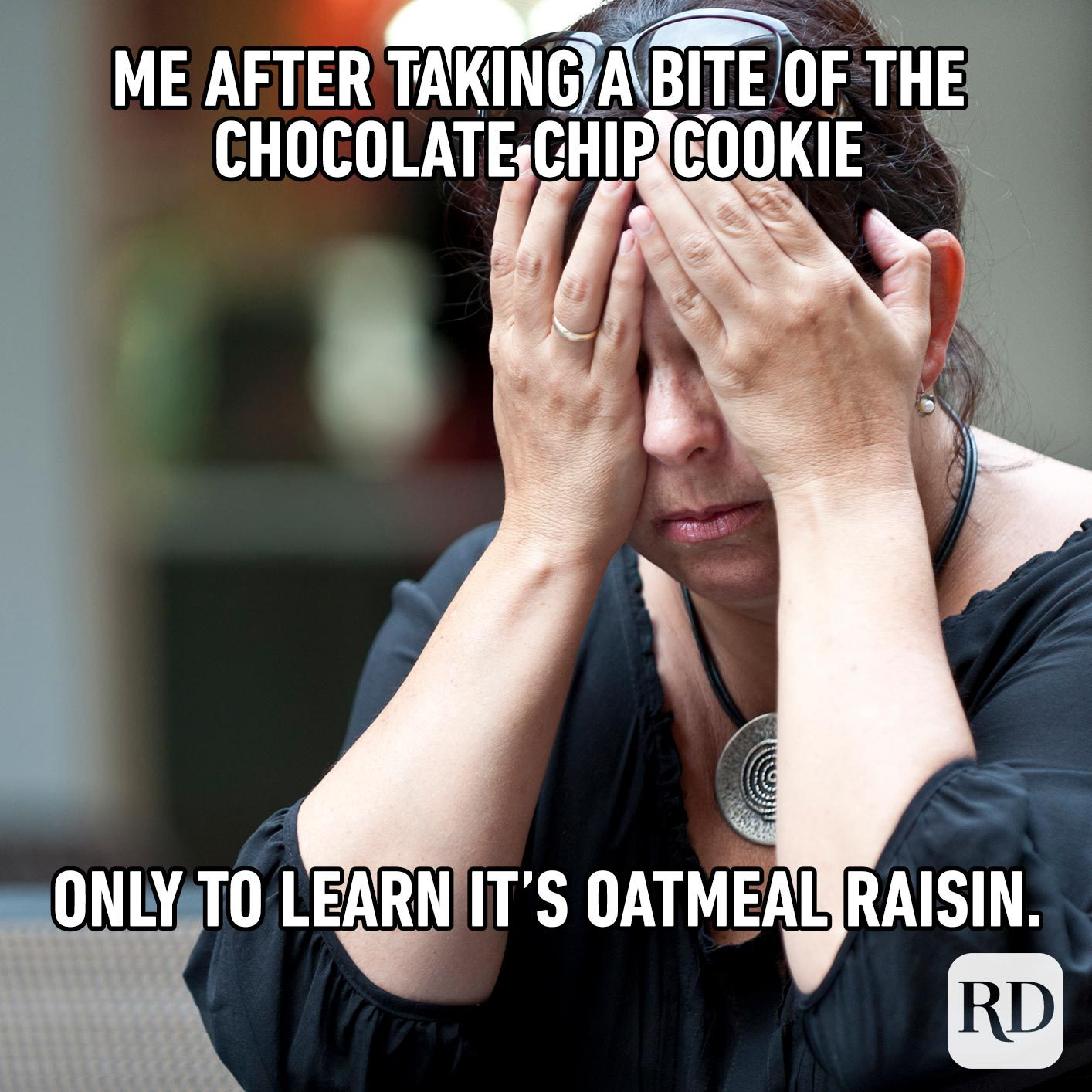 Woman rubbing her eyes with hands. Meme text: Me after taking a bite of the chocolate chip cookie only to learn it's oatmeal raisin.