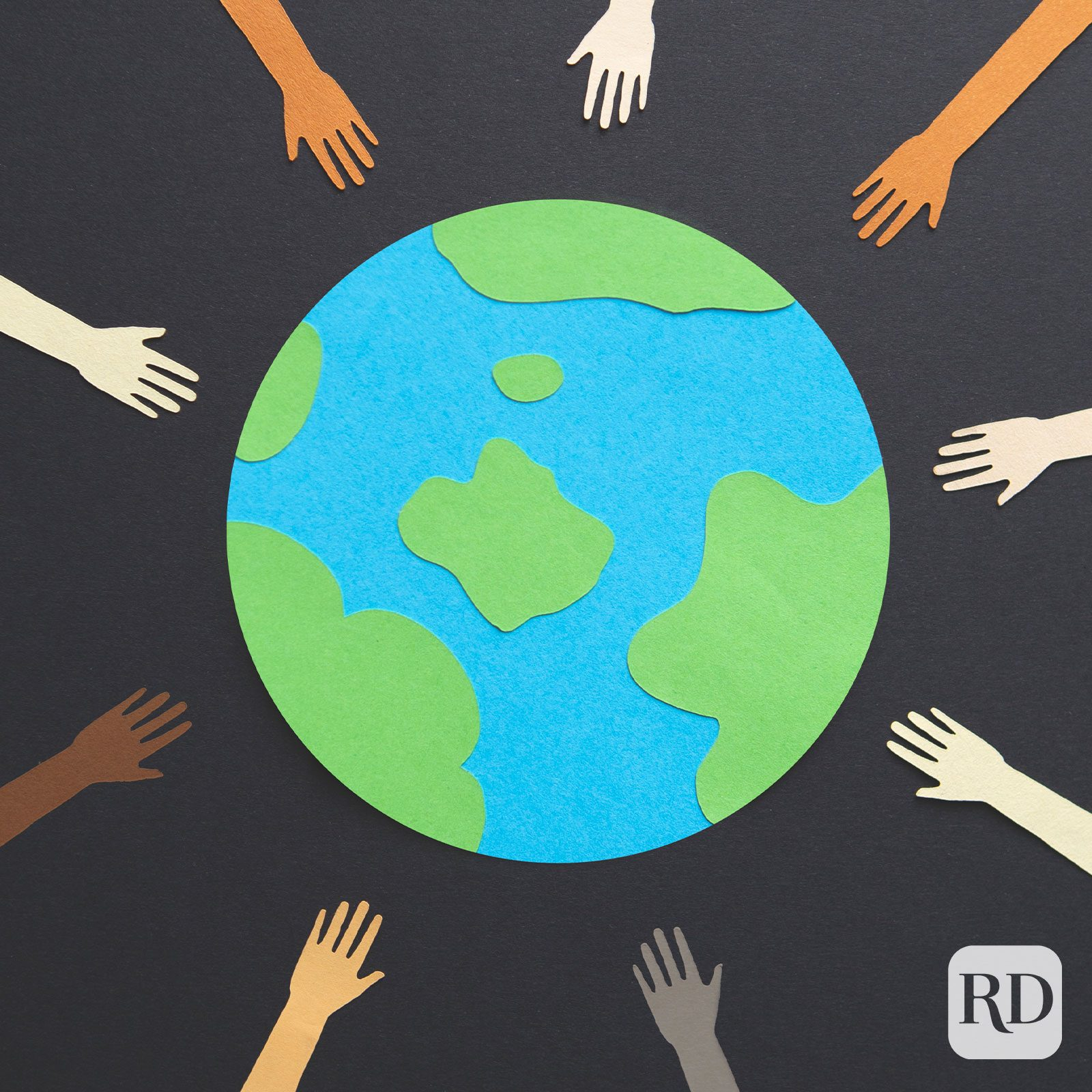 paper cutout of earth surrounded by tiny paper hands