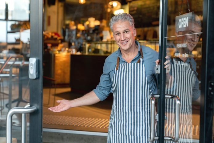 Business owner at the door of a cafe welcoming customers