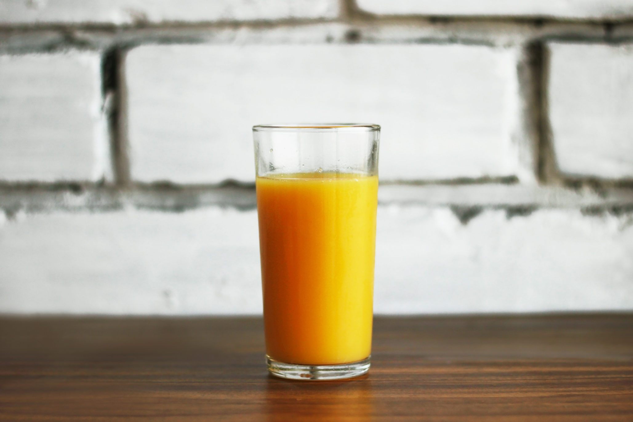 fresh orange juice in a glass on a brick wall background in a loft style