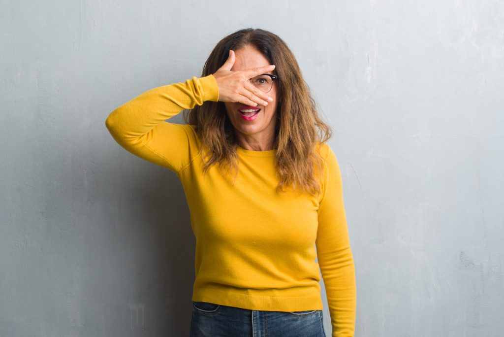Middle age hispanic woman over grey wall wearing glasses peeking in shock covering face and eyes with hand, looking through fingers with embarrassed expression.